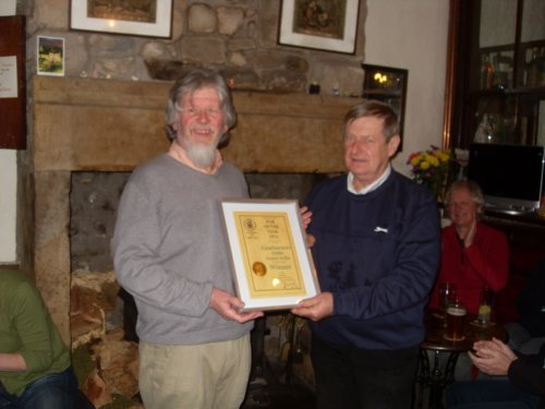 Chairman Michael Dillon presents the certificate to proprieter Joe Moore