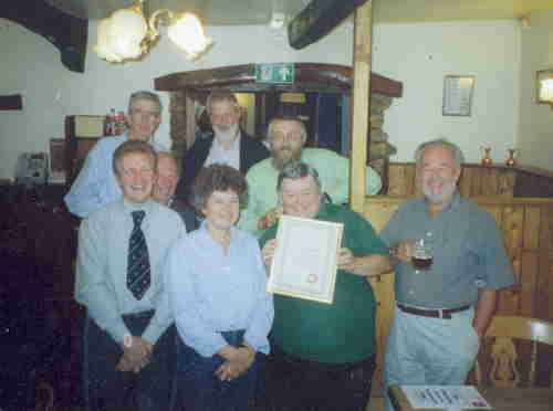 CAMRA members gather round as chairman Jenny Greenhalgh presents Colin Elsdon with an award on his retirement as landlord of the Marton Arms (Thornton-in-Lonsdale)