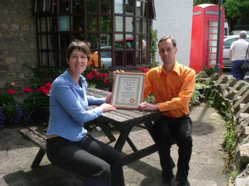 Julie Collinson, licensee of the Priory, receives the Pub of the Year certificate from Cliff Laine, branch chairman