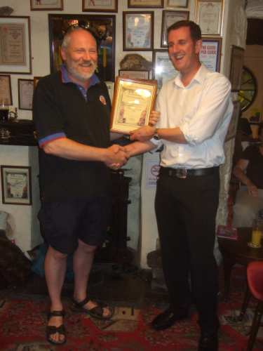 The Cumbria Area Organiser (name required) presents the Pub of the Year certificate to Brian