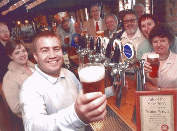 Matt Jackson (front), proprietor of the Water Witch, being presented with his Pub of the Year award by members of this branch (behind bar).